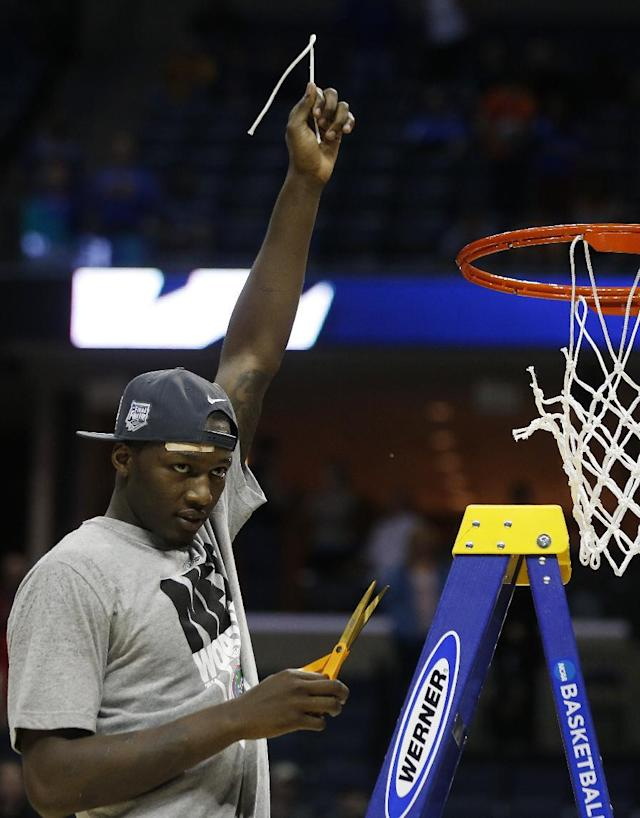 Florida forward Dorian Finney-Smith (10) takes part of the net after the second half in a regional final game against Dayton at the NCAA college basketball tournament, Saturday, March 29, 2014, in Memphis, Tenn. Florida won 62-52. (AP Photo/John Bazemore)