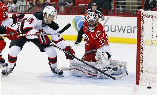 New Jersey Devils' Adam Henrique (14) has his shot deflected wide of the net by Carolina Hurricanes goalie Brian Boucher (33) during the first period of an NHL hockey game in Raleigh, N.C., Saturday, March 31, 2012. (AP Photo/Karl B DeBlaker)