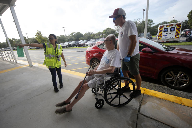Alex Filipovski of Martin County Fire and Rescue helps evacuee Don Penlonas wheel into an evacuation shelter for people with special needs, in preparation for Hurricane Dorian, at Dr. David L. Anderson middle School in Stuart, Fla., Sunday, Sept. 1, 2019. Some coastal areas are under a mandatory evacuation since the path of the storm is still uncertain. (AP Photo/Gerald Herbert)