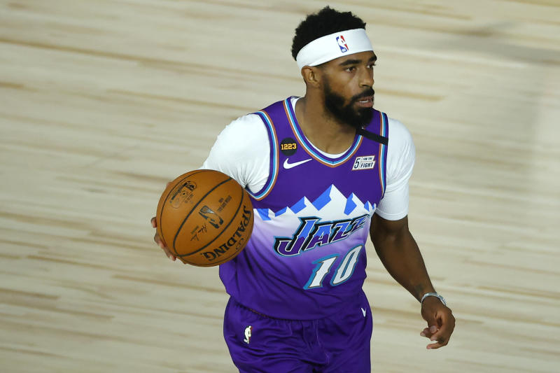 "Mike Conley in a purple jersey that says ""Jazz"" and holding a basketball."
