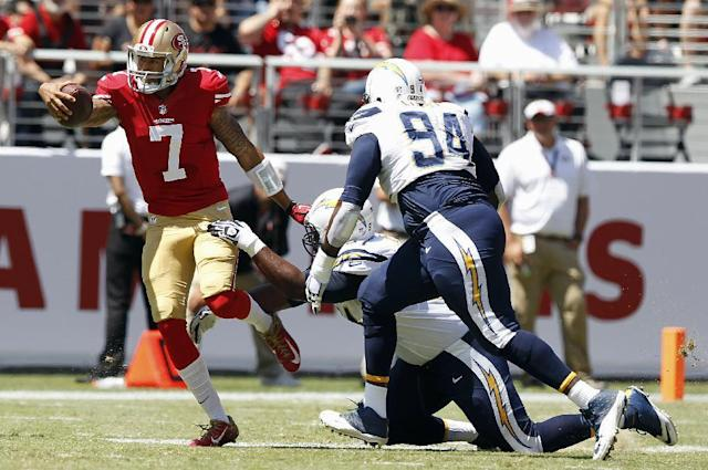 San Francisco 49ers quarterback Colin Kaepernick (7) runs against San Diego Chargers defensive end Kendall Reyes, bottom, and defensive end Corey Liuget (94) during the first quarter of an NFL preseason football game in Santa Clara, Calif., Sunday, Aug. 24, 2014. (AP Photo/Mathew Sumner)