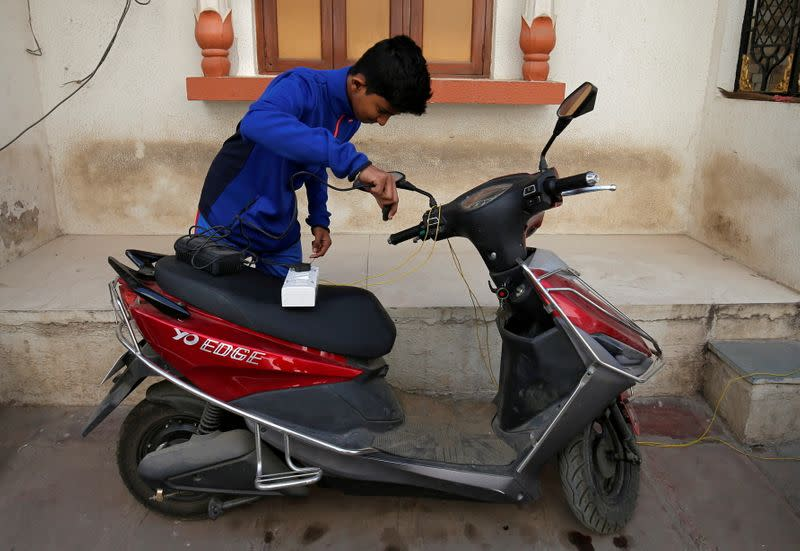 FILE PHOTO: A boy prepares to recharge his electric scooter outside his home in Ahmedabad