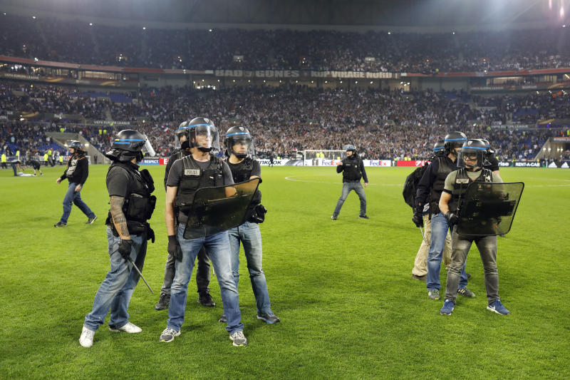 Police officers try to stop supporters as they invade the pitch a few minutes before the Europa League quarterfinal soccer match between Lyon and Besiktas, in Decines, near Lyon, central France, Thursday, April 13, 2017. (AP Photo/Laurent Cipriani)