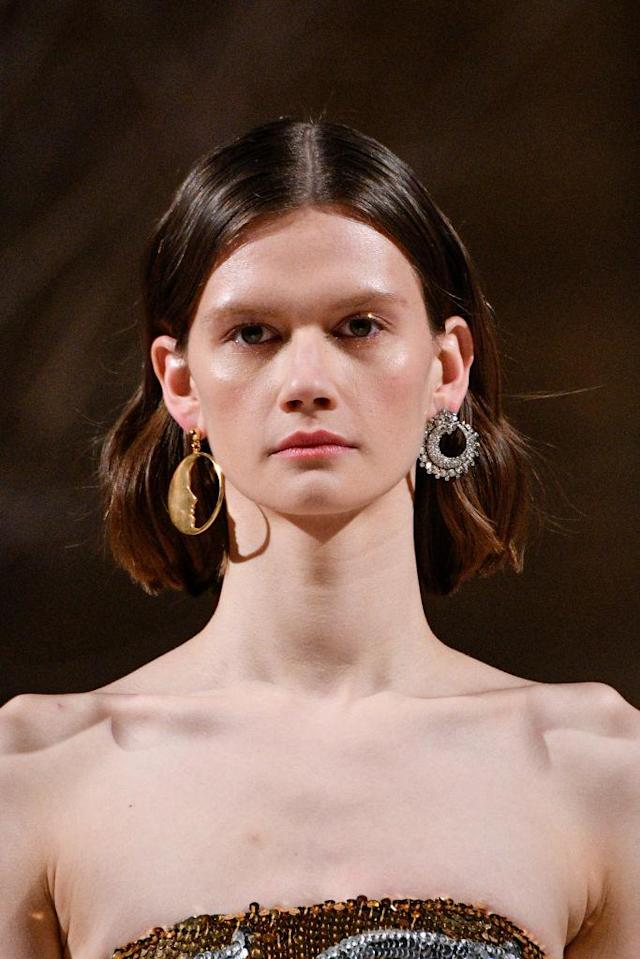 <p>Gold half moon hoop earring and silver crystal-encrusted earring at the Oscar de la Renta FW18 show. (Photo: Getty Images) </p>