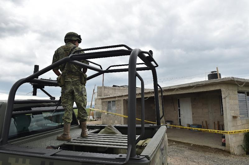 """A soldier stands guard outside the house at the end of the tunnel through which Mexican drug lord Joaquin """"El Chapo"""" Guzman could have escaped from the Altiplano prison, in Almoloya de Juarez, Mexico, on July 12, 2015 (AFP Photo/Yuri Cortez)"""