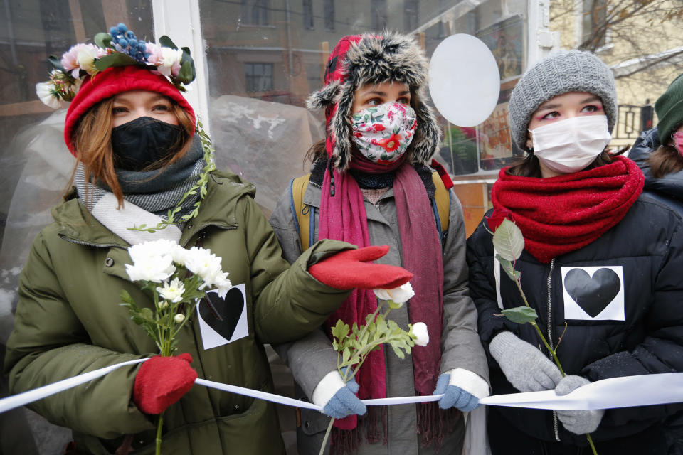 Women, wearing face masks to protect against coronavirus, attend a rally in support of jailed opposition leader Alexei Navalny and his wife Yulia Navalnaya, in Moscow, Russia, Sunday, Feb. 14, 2021. (AP Photo/Alexander Zemlianichenko)