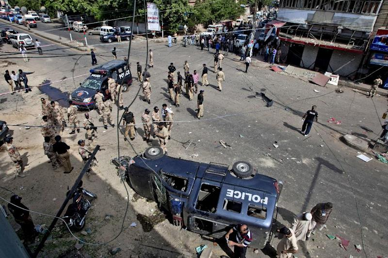 Pakistani security men gather at the site of a bomb blast in Karachi, Pakistan, Wednesday, June 26, 2013. A bomb targeting a senior judge in the southern Pakistani city of Karachi wounded him and killed several security personnel on Wednesday, a senior government official said. (AP Photo/Shakil Adil)