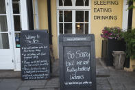Signs outside the Ness pub lay out the COVID protocols they have put in place in Shaldon, Devon, England, Wednesday July 21, 2021. (AP Photo/Tony Hicks)