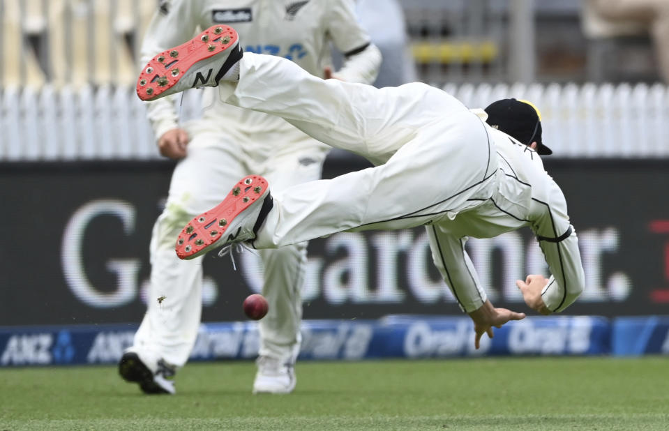 New Zealand's Mitchell Santner is unable to make a diving catch against the West Indies during play on day three of their first cricket test in Hamilton, New Zealand, Saturday, Dec. 5, 2020. (Andrew Cornaga/Photosport via AP)
