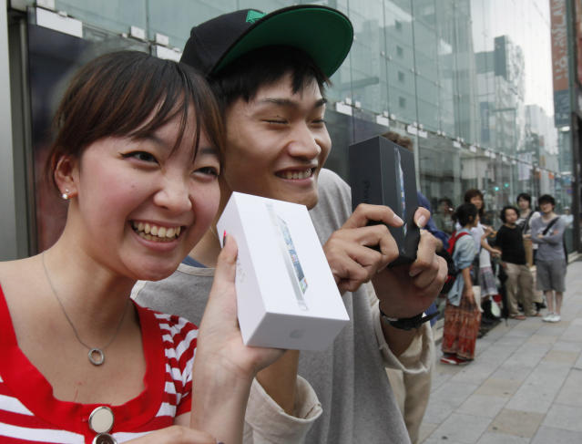 Kae Shibata 20, left, and Yutaro Noji, 21, show off Apple's iPhone 5 after they bought at a store in Tokyo Friday morning, Sept. 21, 2012. (AP Photo/Koji Sasahara)