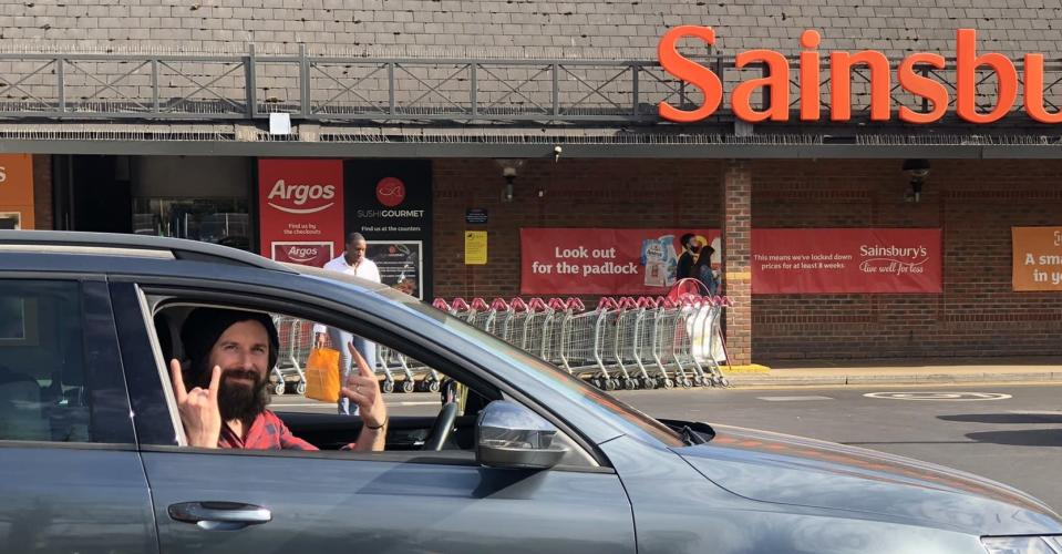 A man sits in a silver car outside a shop which says 'Sainsbury's' and makes the rock sign with both hands