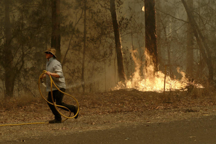 A man runs back to his truck after trying to quench a fire near Moruya, Australia, Saturday, Jan. 4, 2020. Australia's Prime Minister Scott Morrison called up about 3,000 reservists as the threat of wildfires escalated Saturday in at least three states with two more deaths, and strong winds and high temperatures were forecast to bring flames to populated areas including the suburbs of Sydney. (AP Photo/Rick Rycroft)
