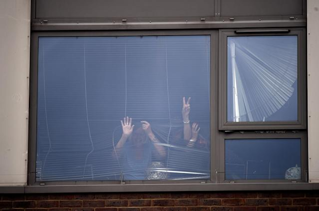 <p>A woman flashes a 'victory' sign at a window in the Burnham Tower residential block, as residents were evacuated as a precautionary measure following concerns over the type of cladding used on the outside of the buildings on the Chalcots Estate in north London, Britain, June 24, 2017. (Photo: Hannah McKay/Reuters) </p>