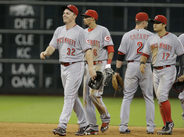 Cincinnati Reds' Jay Bruce (32) leads Billy Hamilton (6), Zack Cozart (2) and Shin-Soo Choo (17) off the field after the Reds beat the Houston Astros in 13 innings of a baseball game Wednesday, Sept. 18, 2013, in Houston. (AP Photo/Pat Sullivan)