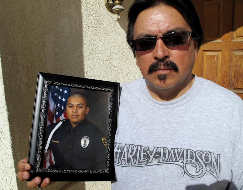 FILE - In this Jan. 30, 2012 file photo in Santa Maria, Calif., Alberto Covarrubias Sr. holds a photo of his son, Santa Maria Police Officer Albert Covarrubias Jr., who was killed by his best friend and fellow officer Matt Kline as police attempted to arrest him for having sex with a minor in the junior police program.  It turns out, inappropriate relationships between officers and youths in the junior police program aren't all that unusual. No organization keeps statistics but an Associated Press examination of news accounts during the 21 years since the Explorers was spun off from the Boy Scouts of America found at least 97 cases involving officers accused of sexual assault on minor girls, and sometimes boys, in the program.  (AP Photo/Tracie Cone, file)