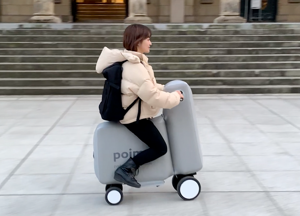 Young woman rides a Poimo inflatable scooter down the sidewalk.