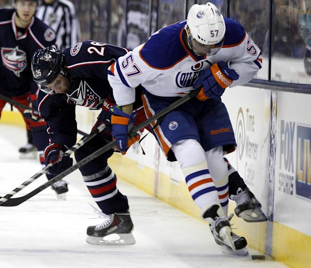 Columbus Blue Jackets' Corey Tropp, left, works for the puck against Edmonton Oilers' David Perron in the second period of an NHL hockey game in Columbus, Ohio, Friday, Nov. 29, 2013. (AP Photo/Paul Vernon)