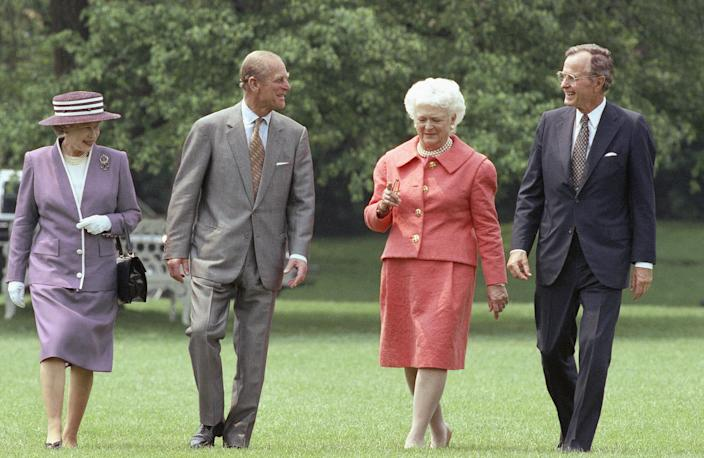 <p>President George H.W. Bush and Mrs. Bush accompany Queen Elizabeth II and her husband, Prince Philip, across the South Lawn of the White House. The Bushes hosted a private lunch for the queen, who arrived in Washington on May 14, 1991, for a nine-day state visit. (Photo: Doug Mills/AP) </p>