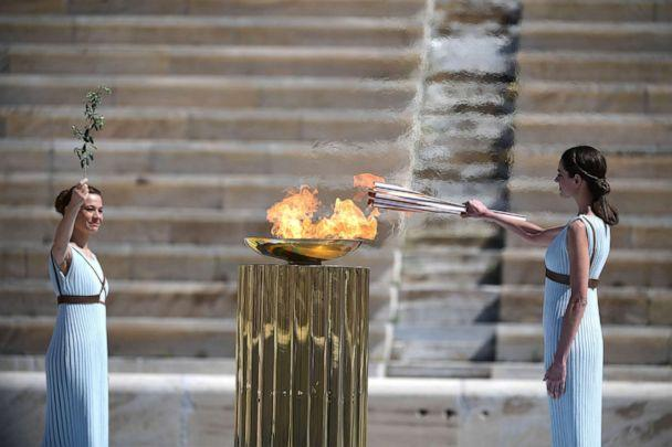 PHOTO: Actresses dressed as ancient Greek high priestesses light the olympic torch during the olympic flame handover ceremony for the 2020 Tokyo Summer Olympics, March 19, 2020, in Athens. (Aris Messinis/AFP/Getty Images)