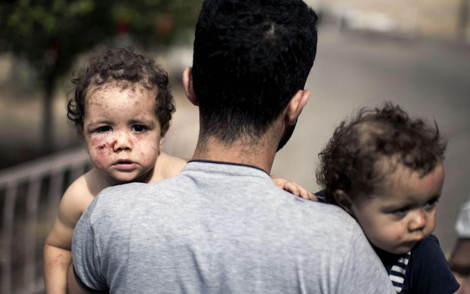 A Palestinian man leaving a hospital holds his daughters after they were injured by an Israeli tank attack during the 2014 Gaza war - MAHMUD HAMS/AFP