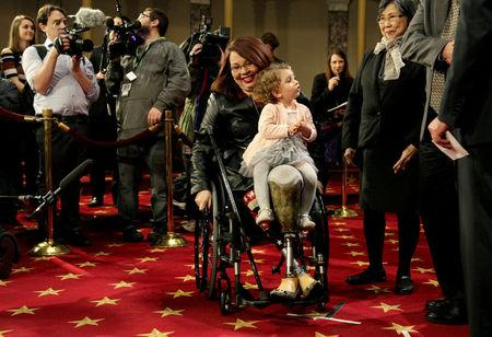 FILE PHOTO: Senator Tammy Duckworth (D-IL) carries her daughter Abigail during a mock swearing in with U.S. Vice President Joe Biden during the opening day of the 115th Congress on Capitol Hill in Washington, U.S., January 3, 2017.  REUTERS/Joshua Roberts/File Photo