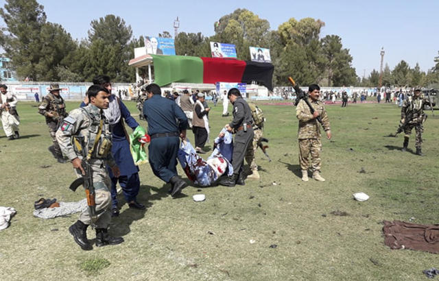 Wounded men are tended to following multiple explosions in Lashkar Gah city of Helmand province, southern Afghanistan, Saturday, Mar. 23, 2019. An Afghan official says that at least three have been killed in twin bomb explosions occurred during the Farmer's Day ceremony in southern Helmand province. (AP Photo/Abdul Khaliq)