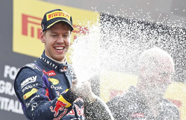 Red Bull Formula One driver Sebastian Vettel of Germany sprays champagne on the podium after winning the Italian F1 Grand Prix at the Monza circuit September 8, 2013. Vettel won the Italian Grand Prix at a canter on Sunday, leading from pole position to celebrate his 32nd career win and third at Monza. REUTERS/Stefano Rellandini (ITALY - Tags: SPORT MOTORSPORT F1 TPX IMAGES OF THE DAY)