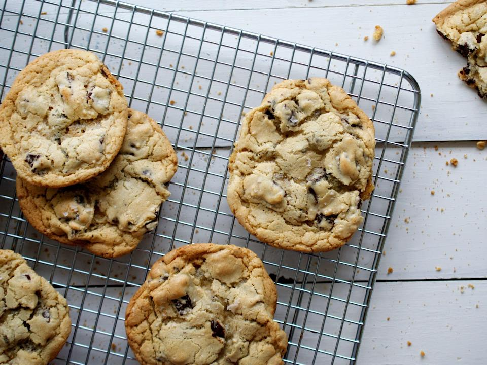 Chocolate chip cookies fresh from oven sit on a wire rack.