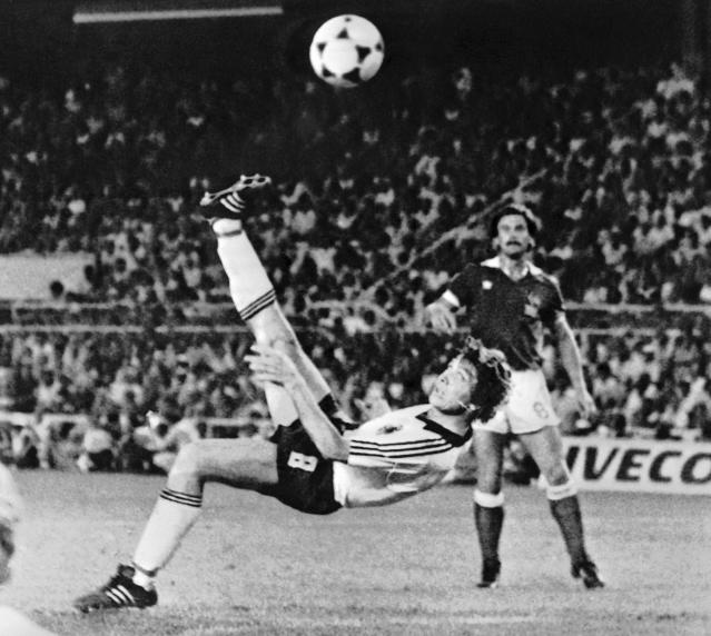 FILE - In this July 8, 1982 file photo, West Germany's Klaus Fischer scores the third goal and equalizes, in the World Cup semifinal soccer match against France, in Seville, Spain. West Germany defeated France in a penalty shoot out after a 3-3 draw. Once again, Germany dug deep Saturday, June 23, 2018 to eke out a victory to keep its World Cup hopes alive. It's something German teams have made a habit of at World Cups. (AP Photo/File)