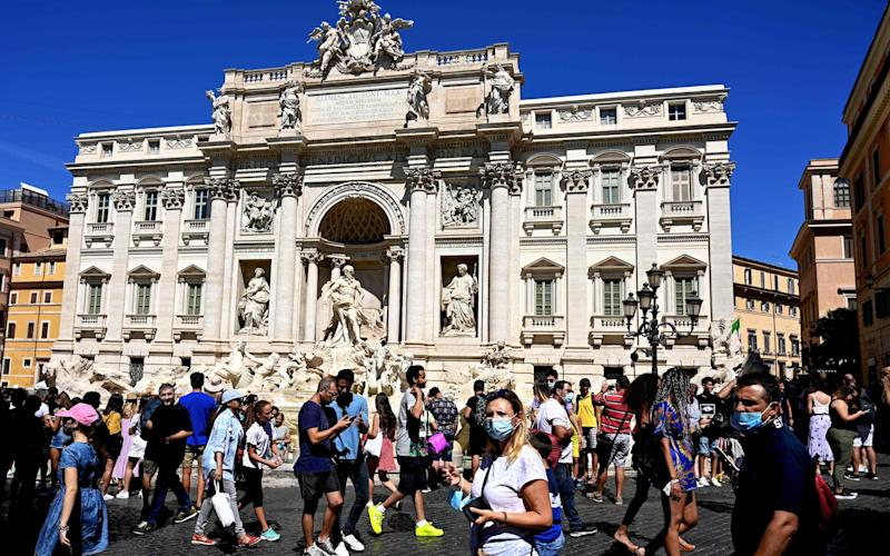 Tourists, some wearing masks, at the Trevi Fountain in Rome - AFP