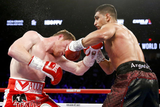 FILE - In this May 7, 2016, file photo, Canelo Alvarez, left, is hit by Amir Khan during their WBC middleweight title fight in Las Vegas. Terence Crawford (34-0, 25 KOs) defends his welterweight title at Madison Square Garden, Saturday, April 20, 2019, against veteran Khan (33-4, 20 KOs), the 2004 Olympic silver medalist from Britain who 15 years later is looking for what could be his biggest victory as a professional. (AP Photo/Isaac Brekken, File)
