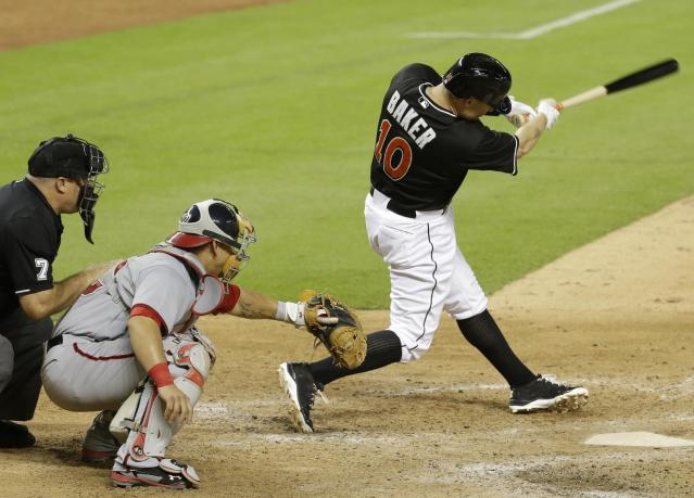 Miami Marlins' Jeff Baker (10) hits a single to drive in Adeiny Hechavarria for the game-winning run in the ninth inning during a baseball game against the Washington Nationals, Monday, July 28, 2014, in Miami. The Marlins defeated the Nationals 7-6. At left is Washington Nationals catcher Wilson Ramos. (AP Photo/Lynne Sladky)