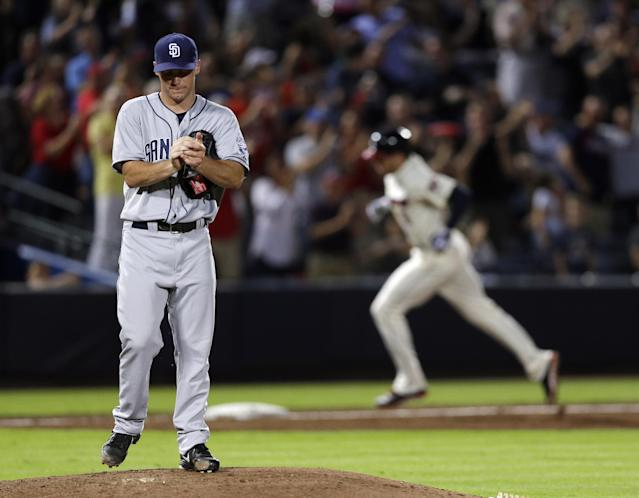 San Diego Padres starting pitcher Robbie Erlin, left, breaks in a new baseball as Atlanta Brave' Freddie Freeman, right, rounds third base after hitting a home run in the sixth inning of a baseball game in Atlanta, Saturday, Sept. 14, 2013. (AP Photo/John Bazemore)