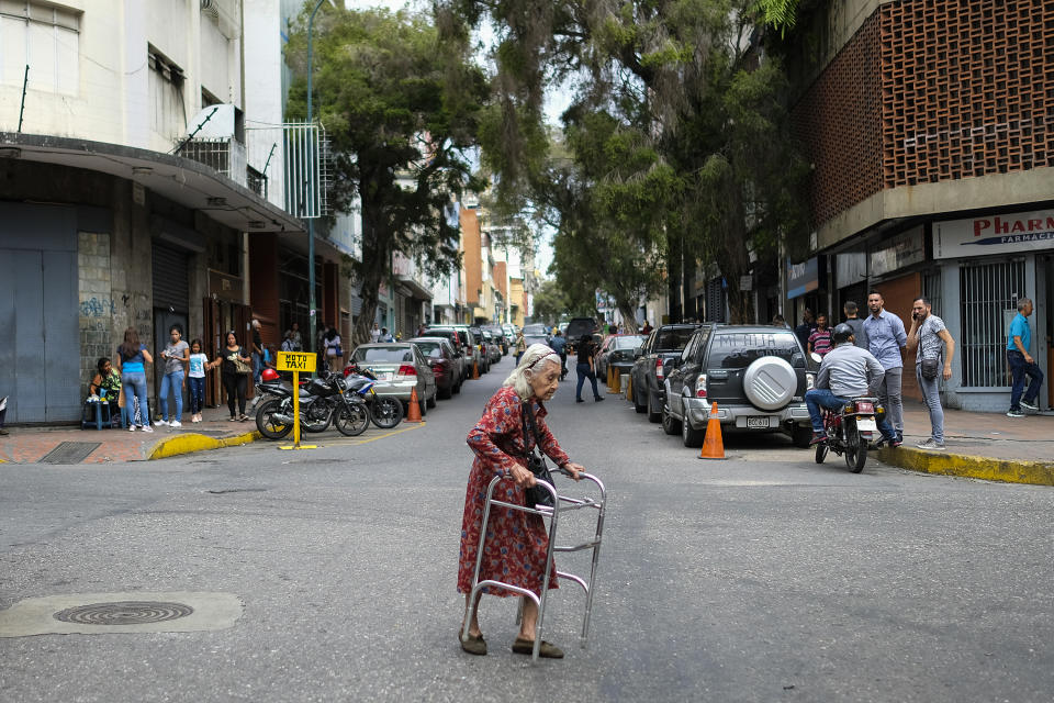 An elderly woman crosses a street in Caracas on July 22, 2019. - Venezuela is wracked by an economic crisis after five years of crippling recession in which its population has faced many hardships such as a shortage of basic necessities and failing public services. (Photo by Matias Delacroix / AFP)        (Photo credit should read MATIAS DELACROIX/AFP via Getty Images)