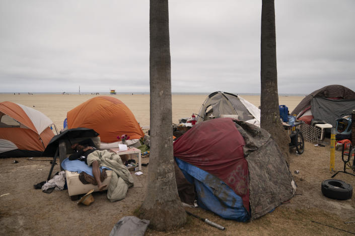 A homeless man naps in an encampment set up along the boardwalk in the Venice neighborhood of Los Angeles, Tuesday, June 29, 2021. The proliferation of homeless encampments on Venice Beach has sparked an outcry from residents and created a political spat among Los Angeles leaders. (AP Photo/Jae C. Hong)