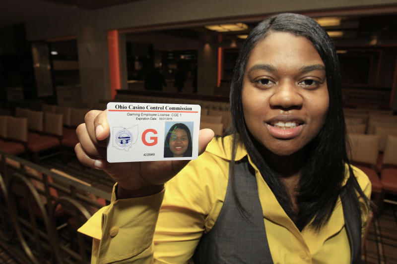 Taneshia Pitts, 28, holds up the first gaming employee license issued at the Horseshoe Casino in Cleveland Thursday, April 5, 2012. The commission has approved more than 1,100 licenses and is investigating more than 500 other applicants. The Cleveland casino opens during the week of May 14. Toledo's will open two weeks later and casinos in Cincinnati and Columbus will open next year. (AP Photo/Tony Dejak)