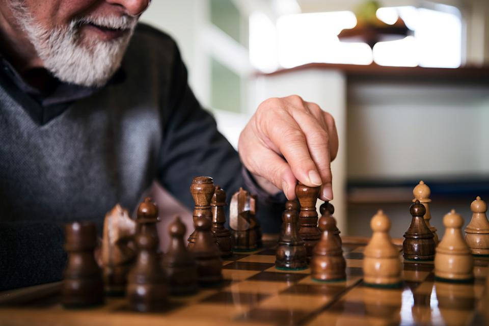 A senior bearded man is playing a chess game at home with his wife. Close-up view of an older man who is making a chess move with a chess piece.