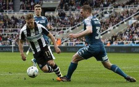 Newcastle United's Matt Ritchie (L) has a penalty appeal turned down after this challenge by Wigan Athletic's Jake Buxton