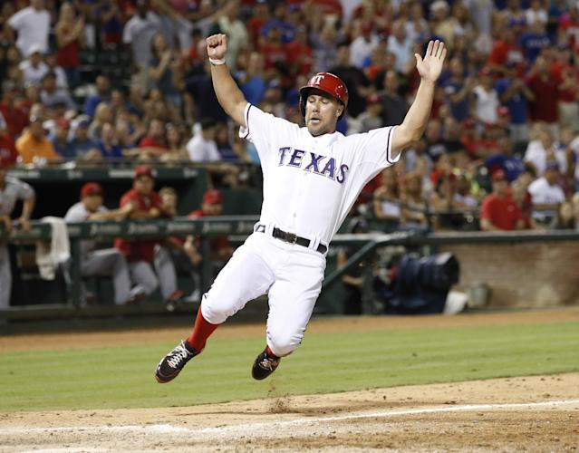 Texas Rangers' David Murphy slides home ahead of the throw to Los Angeles Angels catcher Chris Iannetta during the seventh inning of a baseball game, Tuesday, July 30, 2013, in Arlington, Texas. (AP Photo/Jim Cowsert)