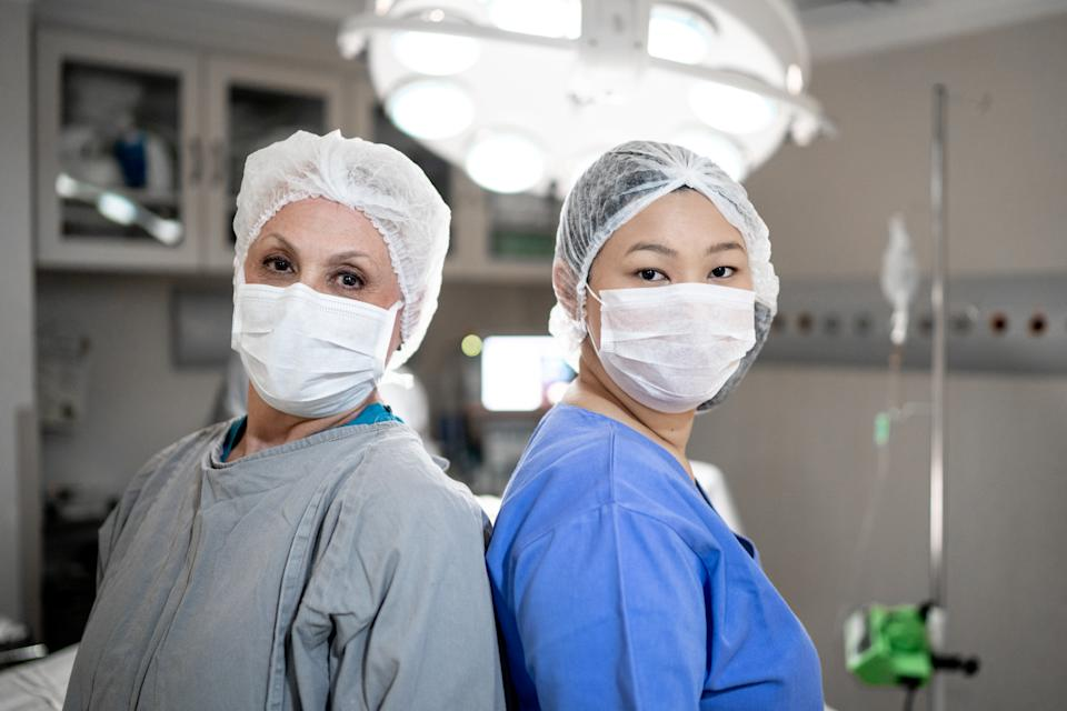 Portrait of female healthcare coworkers with face mask on operating room at hospital. Photo: Getty