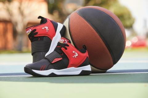 A pair of red, black, and white Shaq by Skechers basketball shoes sitting on a court with a basketball.