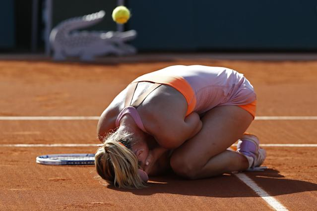 Russia's Maria Sharapova falls to the ground as the match ball bounces back as she wins the final of the French Open tennis tournament against at the Roland Garros stadium, in Paris, France, Saturday, June 7, 2014. Sharapova won in three sets 6-4, 6-7, 6-4. (AP Photo/Darko Vojinovic)