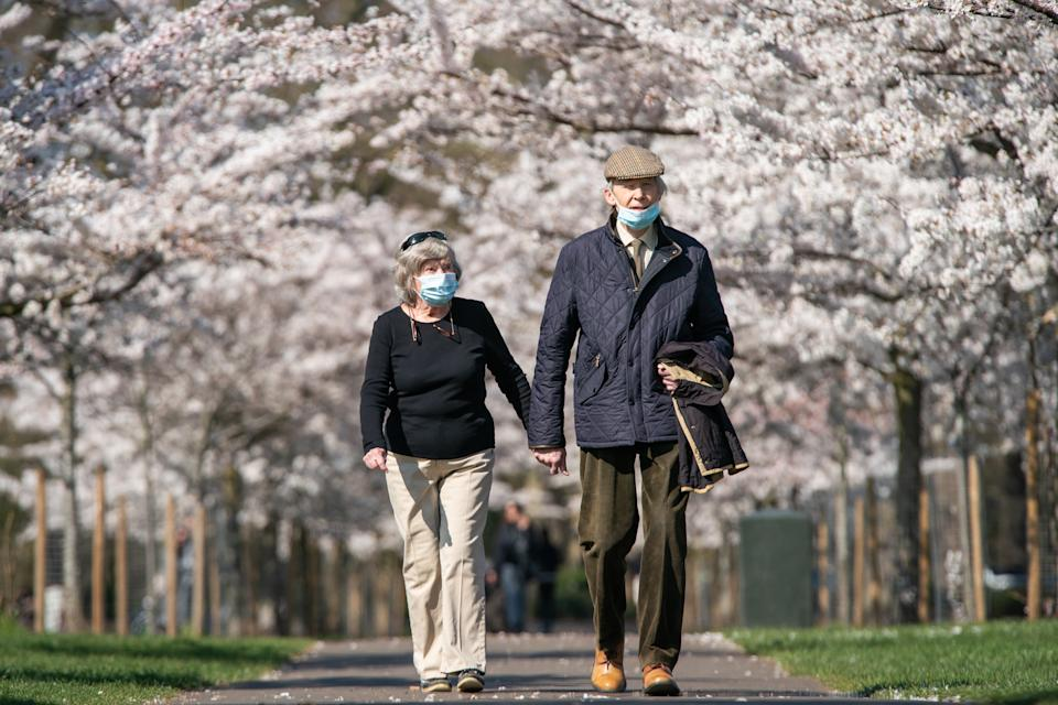 Members of the public walk down along a path lined with blossoms in Battersea Park, London. Picture date: Monday March 22, 2021. (Photo by Aaron Chown/PA Images via Getty Images)