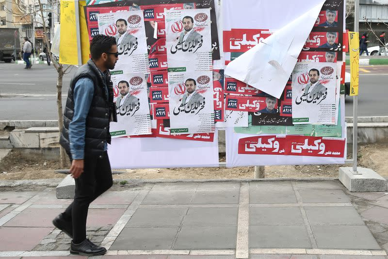 A man walks past parliamentary election campaign posters in Tehran