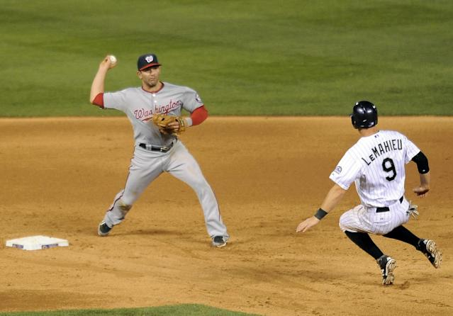 Colorado Rockies DJ LeMahieu, right, is forced out at second base by Washington Nationals second baseman Danny Espinosa in the sixth inning of a baseball game on Tuesday, July 22, 2014, in Denver. (AP Photo/Chris Schneider)