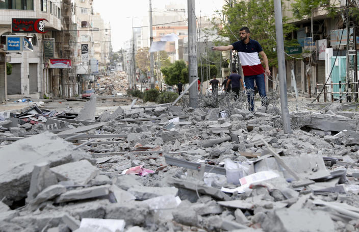 A man inspects the rubble of destroyed commercial building and Gaza health care clinic following an Israeli airstrike on the upper floors of a commercial building near the Health Ministry in Gaza City, on Monday, May 17, 2021. (AP Photo/Adel Hana)