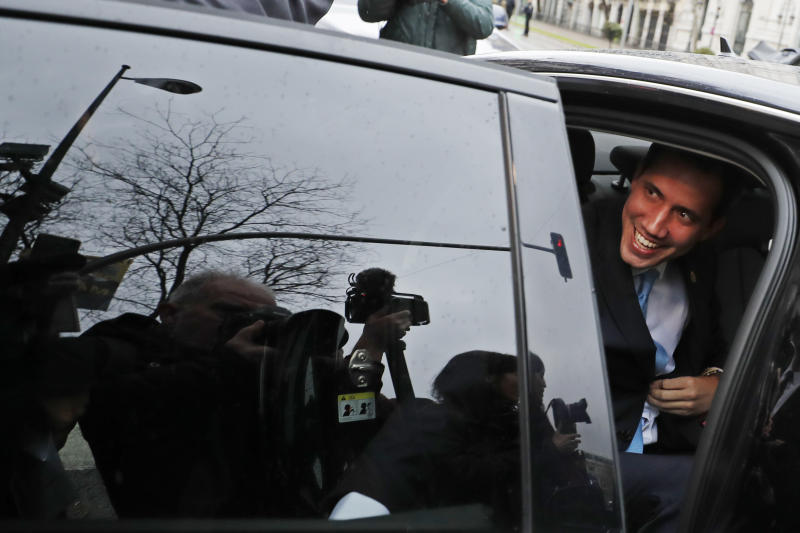 The leader of Venezuela's political opposition Juan Guaido smiles from a car during a visit to Madrid, Spain, Saturday, Jan. 25, 2020. Juan Guaido, the man who one year ago launched a bid to oust Venezuelan President Nicolas Maduro, arrived Saturday in Spain, where a thriving community of Venezuelans and a storm among Spanish political parties awaited him. (AP Photo/Paul White)