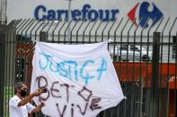 """A man takes a picture next to a banner that's reads: """"Justice. Beto lives"""", after Joao Alberto Silveira Freitas was beaten to death by security guards at a Carrefour supermarket in Poro Alegre"""