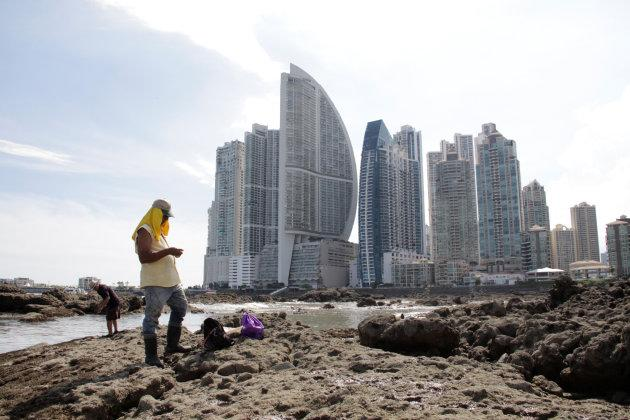People stand on rocks on the shore during low tide as the Trump Ocean Club International Hotel and Tower Panama (3rd from left) is seen next to apartment buildings in Panama City, Panama October 11, 2017.