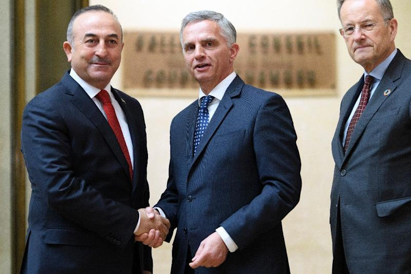 Turkey's Foreign Minister Mevlut Cavusoglu (L) shakes hands with Swiss sounterpart Didier Burkhalter (C) as Director General of the UN Office in Geneva Michael Moller looks at UN headquarters in the Swiss city on January 12, 2017 (AFP Photo/LAURENT GILLIERON)